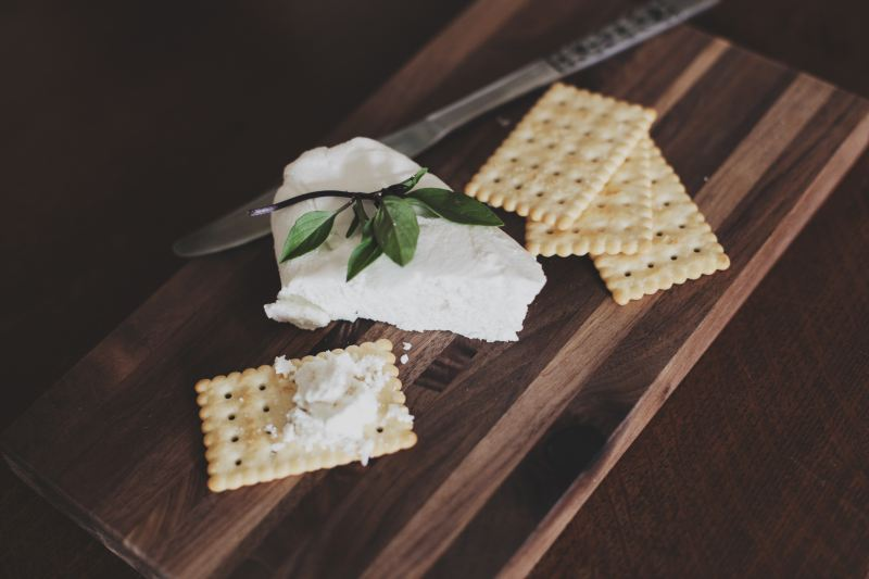White rectangular crackers sit on a nice cutting board next a chunk of white goat cheese and a green piece of garnish.