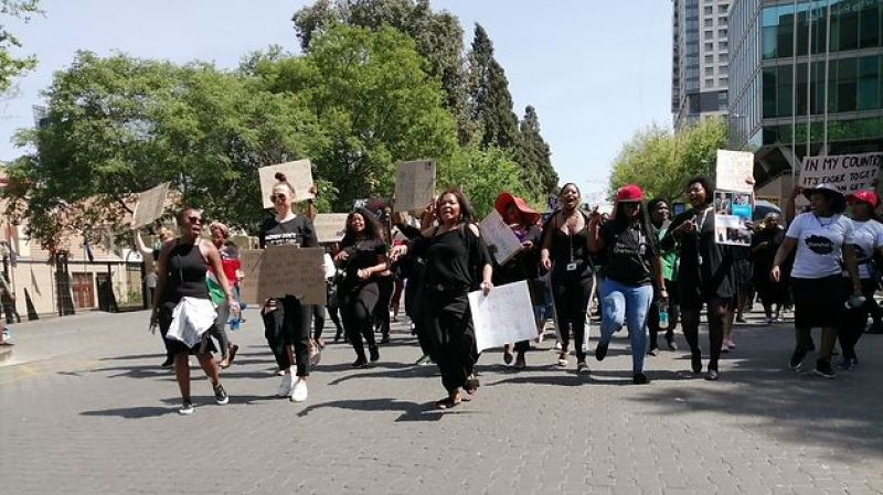 A large group of black women wearing only black or white walk down a paved road holding protest signs: Demonstrators during the #SandtonShutdown march in Johannesburg on September 13th, 2019.