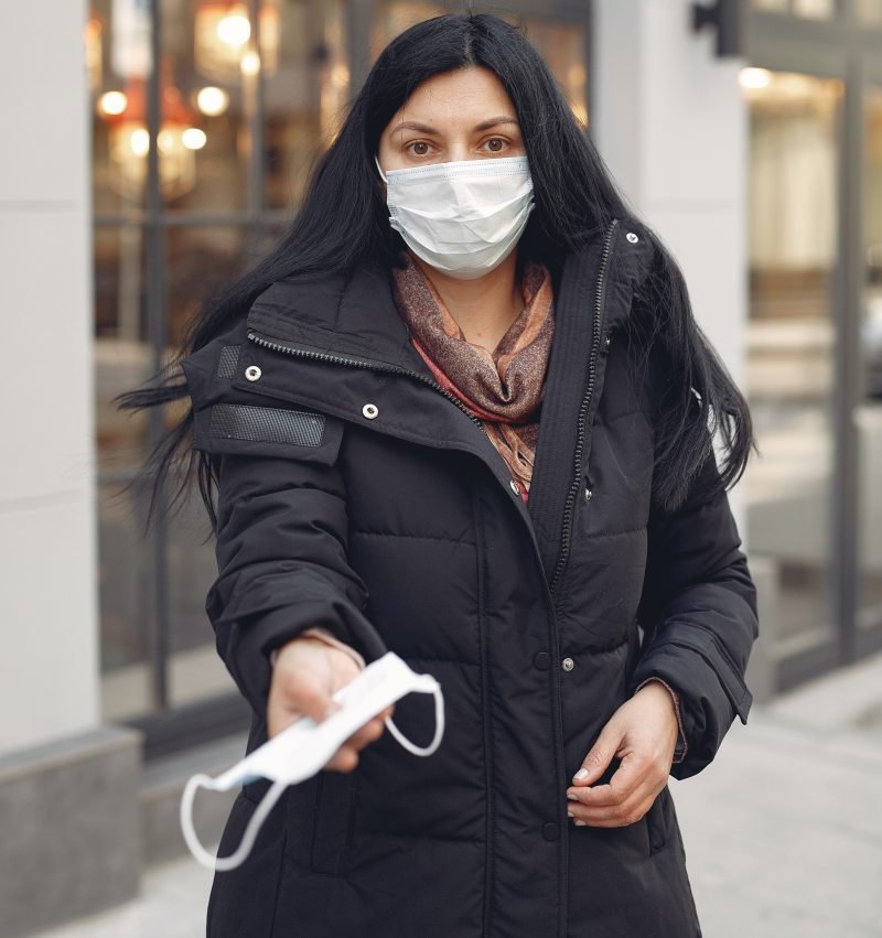 A medium-skinned woman with long black hair worn down, a puffy black jacket, and a white surgical mask over her face, offers another surgical mask to the person behind the camera, her eyes pleading.
