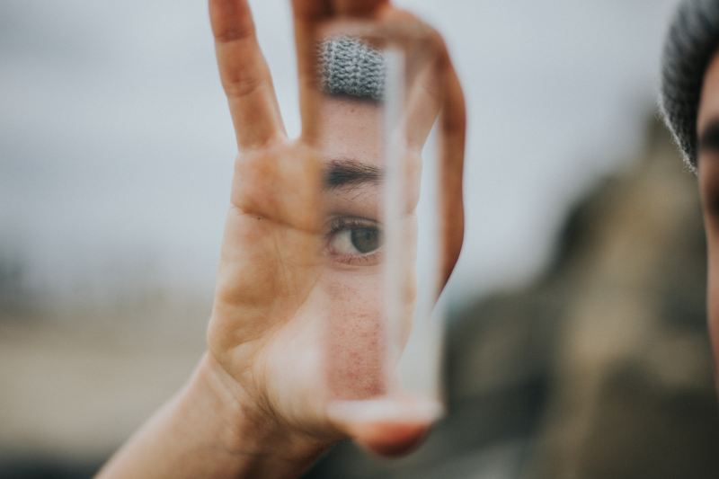 A hand holds up a piece of glass, in which you can see the reflection of a person's eye. It is not clear whether it is their own eye or someone else's.