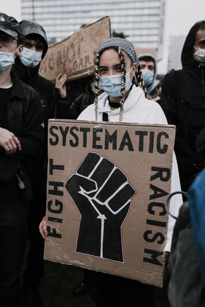 """a group of protestors of many skin-tones closely packed, wearing blue face masks. The person in front has two tight braids falling in front of their face that are a mixture of very dark & very blonde hair. They hold a sign that says """"Fight Systemic Racism"""" with the Black Power fist below."""