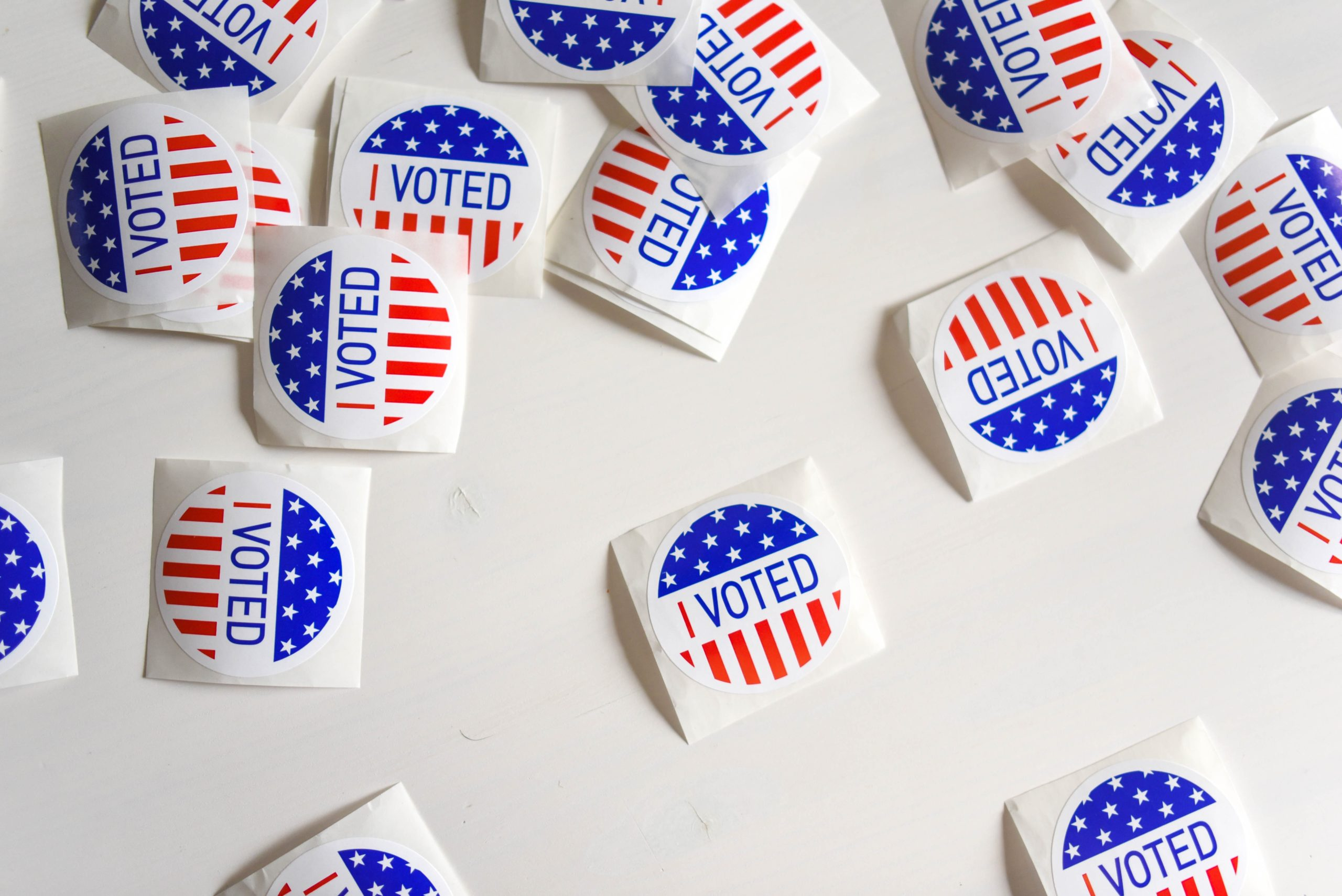 """A white table covered in circular """"I voted"""" stickers with American flags on them."""