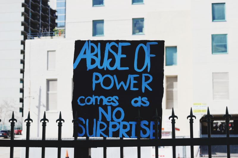 """A black cardboard sign with bright blue lettering sit on and iron fence, It reads, """"Abuse of power comes as no surprise"""""""