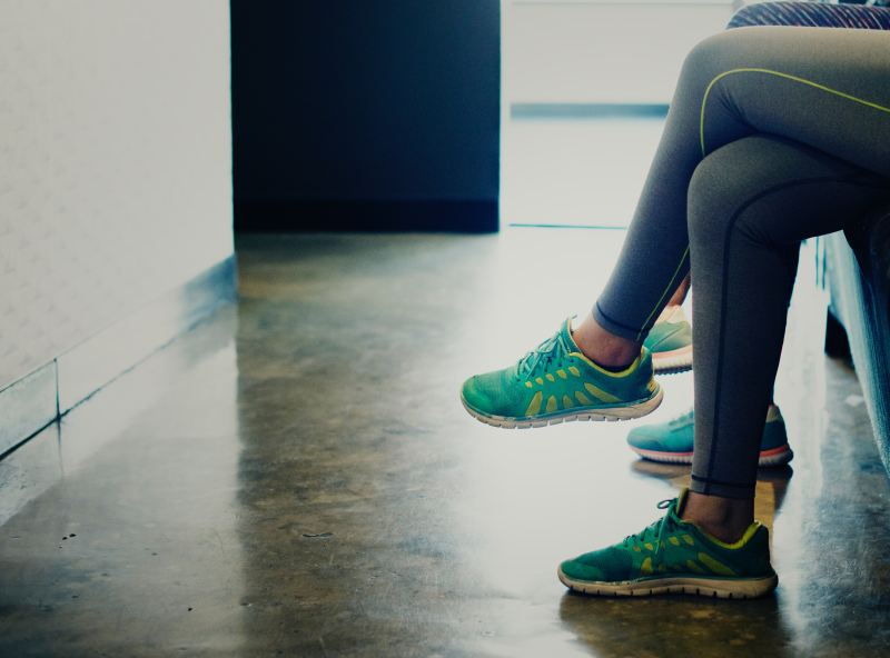 Two people wearing exercise leggings and colorful running shoes sit in a waiting room that is otherwise empty.