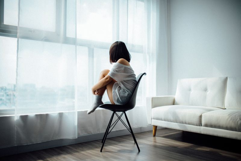 A woman sits in a chair, hugging her knees to her chest, as she stares through sheer blinds and the window. The room is empty and airy around her, and she's clearly alone.