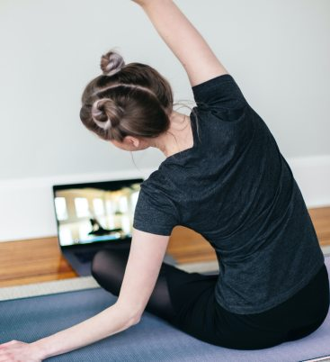 A young light-skinned woman wearing dark fitness clothes and two buns at the top of her head, sits crosslegged on a yoga mat, her arm stretched above and over her so that she's leaning to the left, imitating the yoga pose of the instructor seen on her laptop screen in front of her.