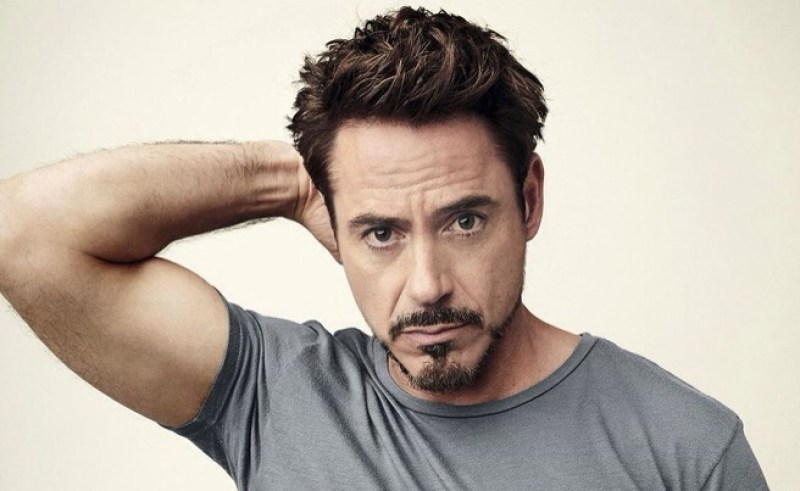 Character Tony Stark: A white man in his 40's with dark hair cut short and styled, and dark facial hair that emphasizes his jawline. Wearing a grey t-shirt, he is holding his hand behind his head, which showcases his bicep muscles, while staring moodily into the camera.