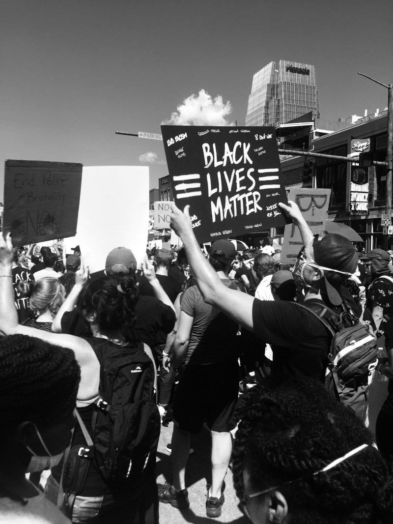 "Black and white photo of BLM protest in Nashville, TN. A densely packed crowd walks through the street, a nearby protestor holding a black sign with white letters that says ""Black Lives Matter"" with three parallel white lines on either side."
