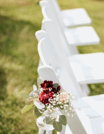A row of white outdoor wedding chairs on a green lawn. The closest to the camera is decorated with red, pink, and white flowers in a small glass jar.