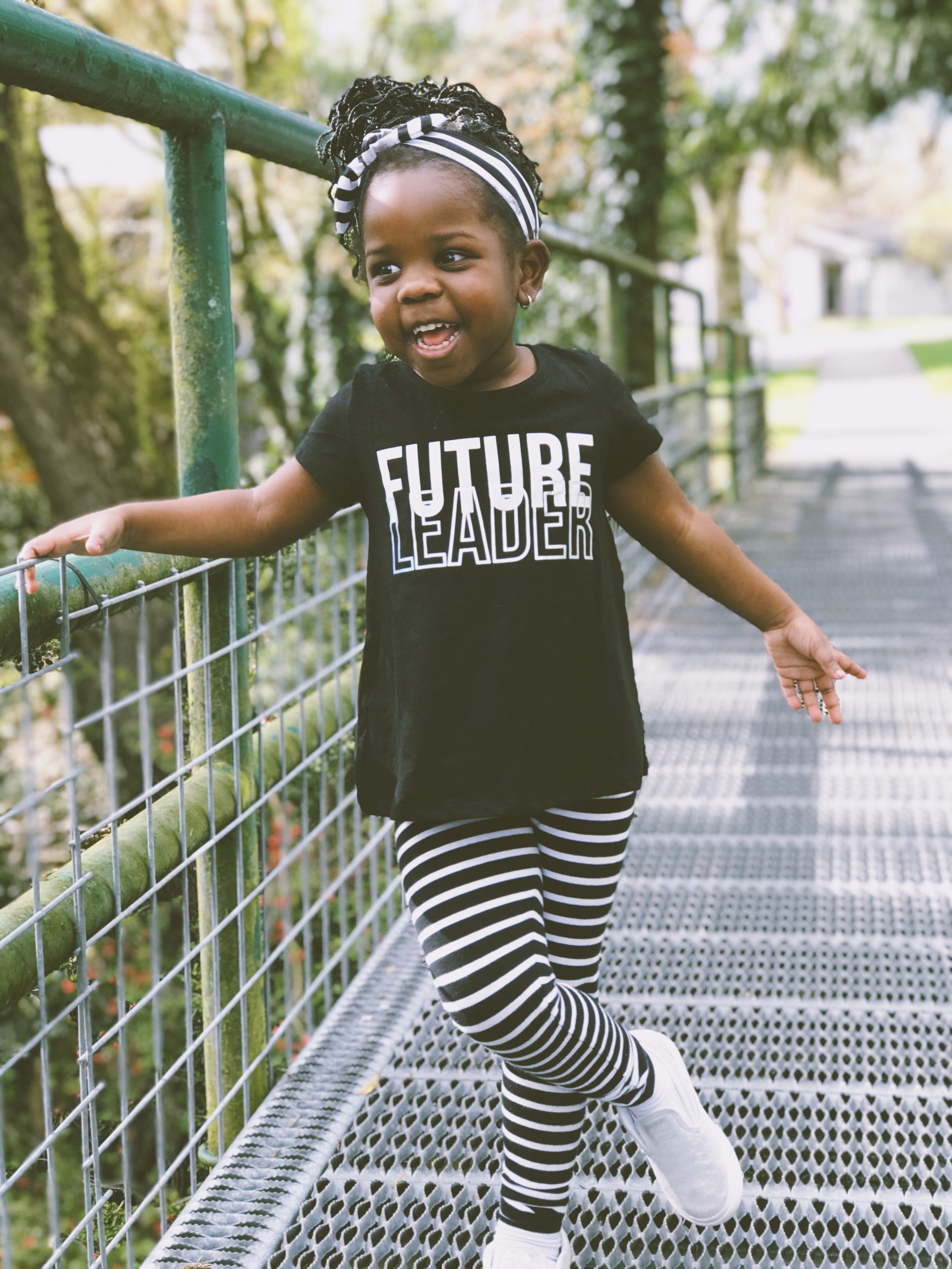 """A very young black girl wears a spunky grin, natural hair, a head wrap, and a black and white shirt that says """"Future Leader."""""""