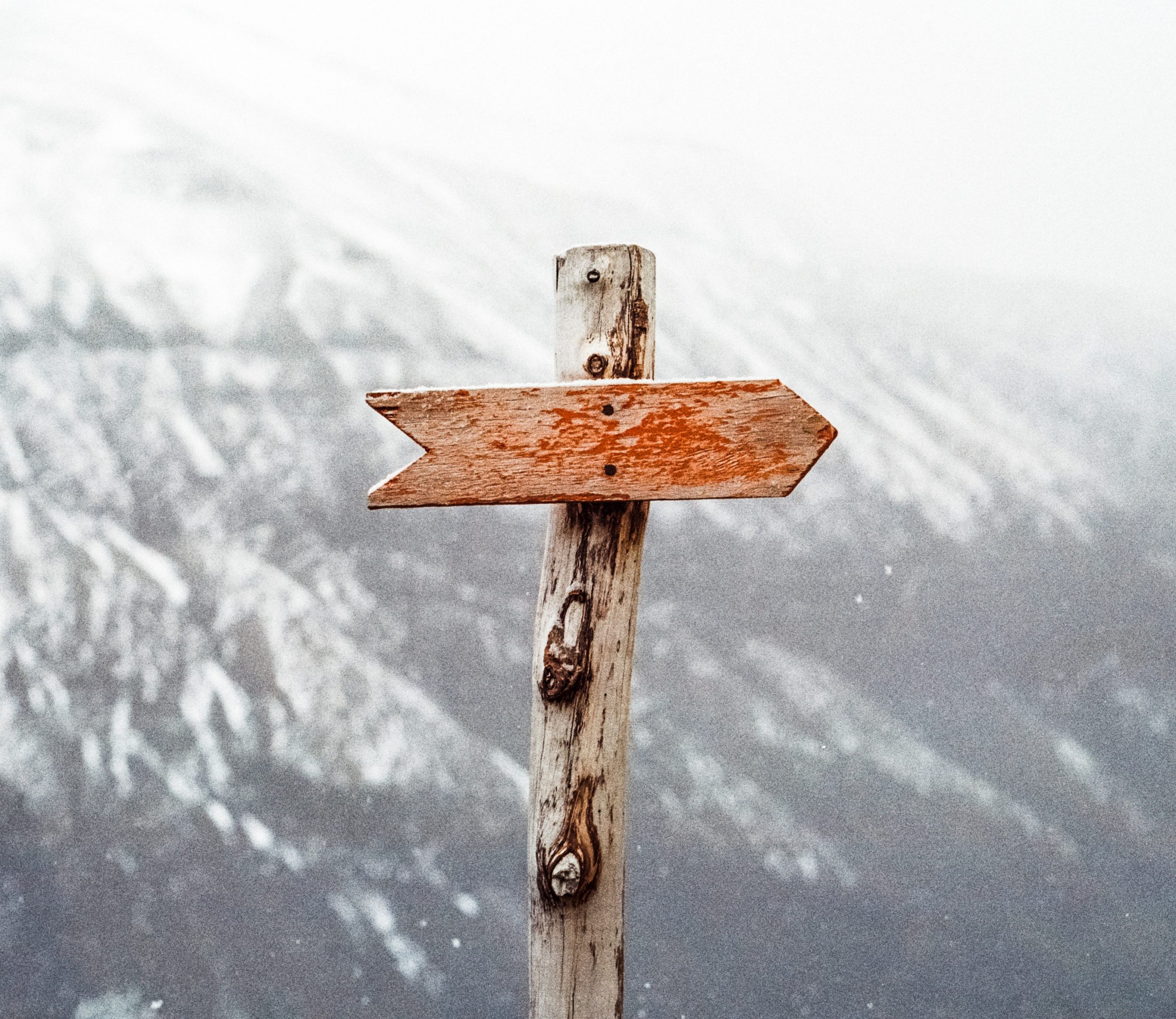 A knobby wooden post sports an arrow shaped sign with nothing by scratches and faded red paint-- no name. It stands in front a large snowy mountain.