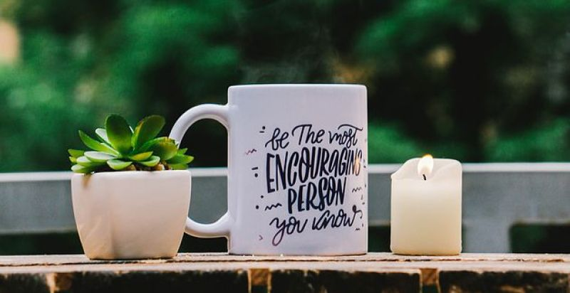 "A white mug with cursive writing says. ""be the most encouraging person you know"" and it sits between a lit candle, a green succulent in a white pot, and a green tree in the background."