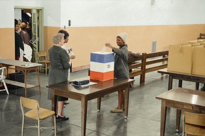 A colorized photo from 1964: A black woman casts her ballot into a red, white and blue box, as several other black women wait in line to cast their own ballots.