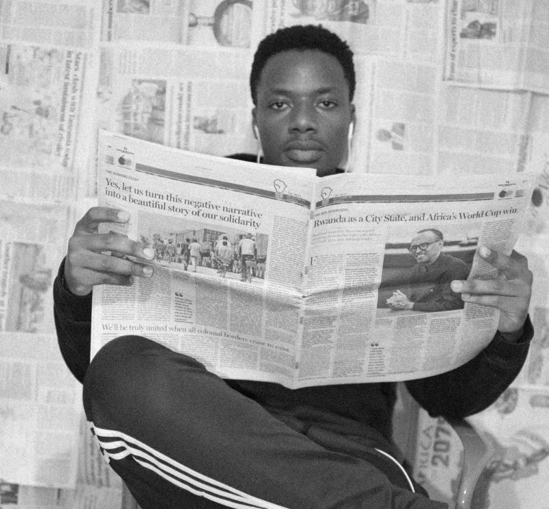 A man with dark skin and short natural black hair sits in front of a wall covered in newspapers. He is holding an open African Newspaper, while he stares at the camera head on.