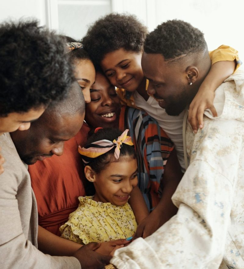 A family of 7 black people of varying ages and skin tones comes in close for a group hug, all smiling, a young girl with a yellow dress and matching hairbow at the center of the hug.