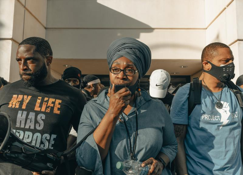 "A middle aged black woman wearing a grey-blue head wrap and blouse speaks into the mouth piece of a loud speaker, which a black man standing next to her is holding. His shirt reads ""My Life Has Purpose"". They, and many other black people, are standing together at an outdoor protest."