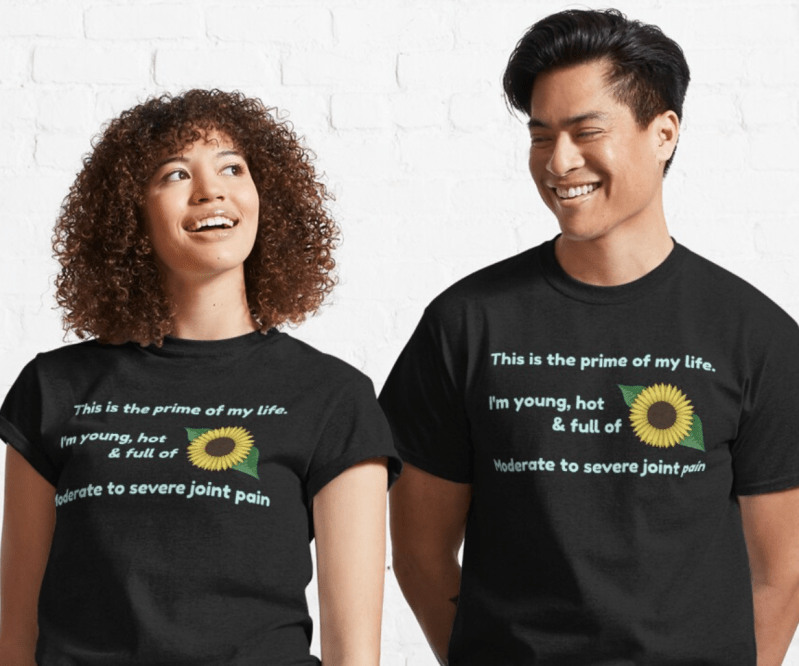 The design described above but with a black background and pale turquoise text. It is demoed on standard black T-shirts worn by a man and a woman of color who are smilng.