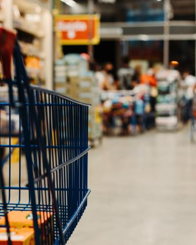 A black grocery cart headed down an empty aisle at the grocery store. The perspective is from the grocery cart level directly to the right of the front.