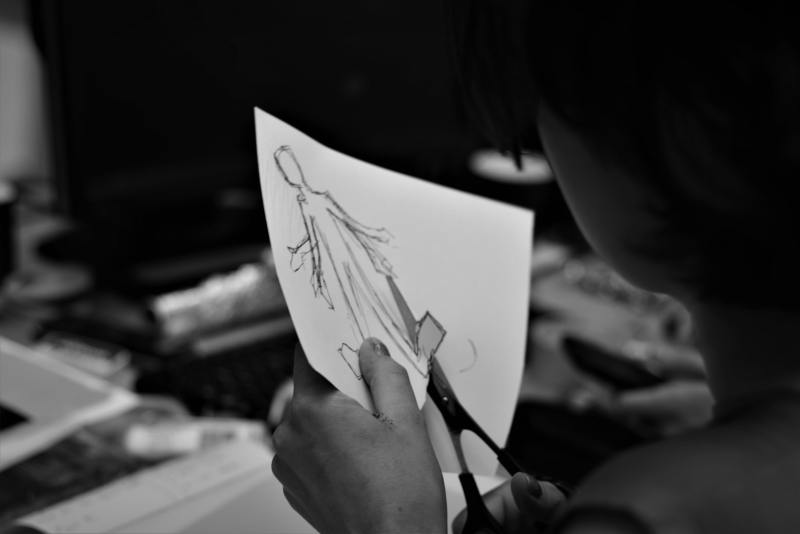 A black and white photo of a person cutting out a drawn figure with no features on a piece of paper, with a pair of scissors. The person's face isn't visible and their background is blurry.