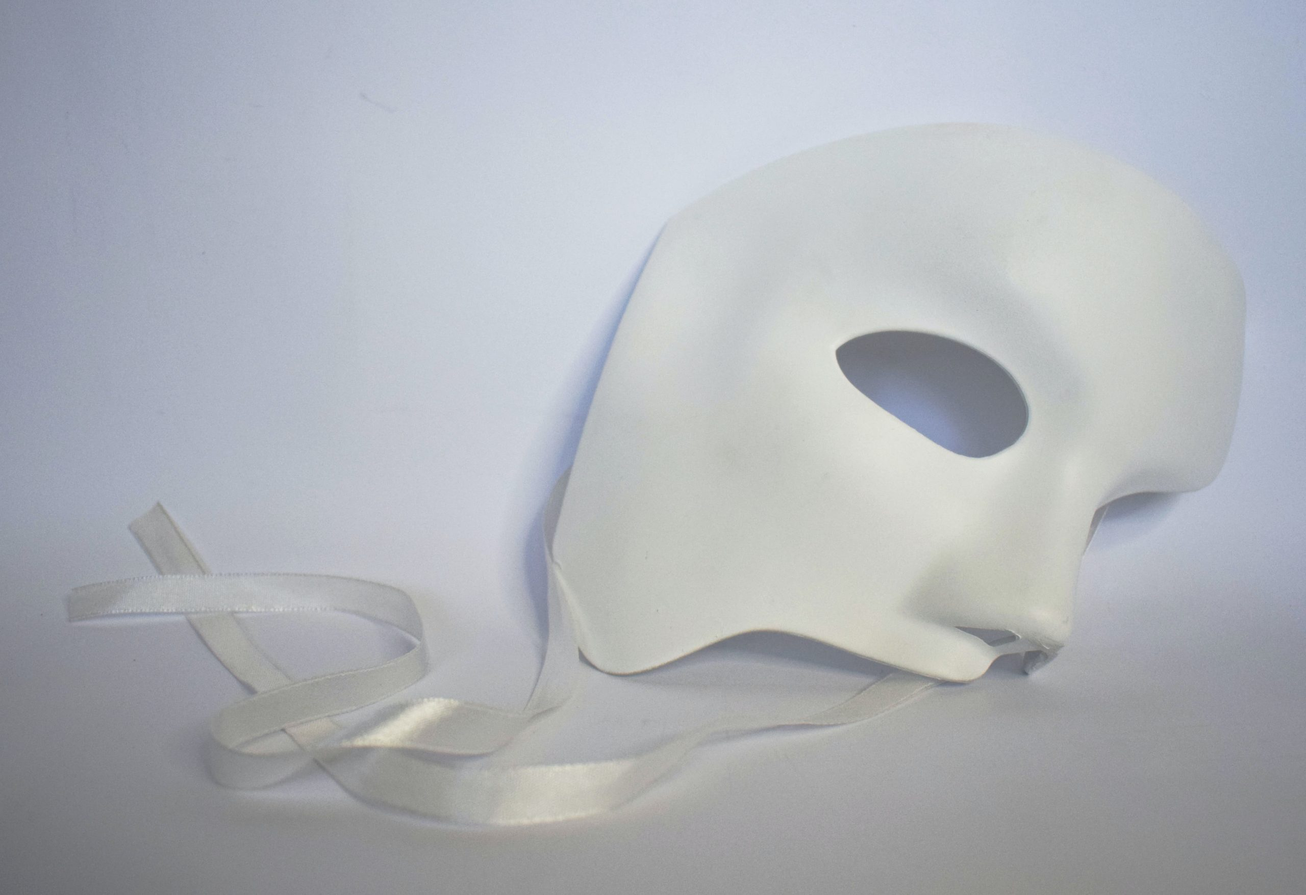 A white theater mask that covers only right upper half of the face, with white silk ribbons, sits upright against a white background.