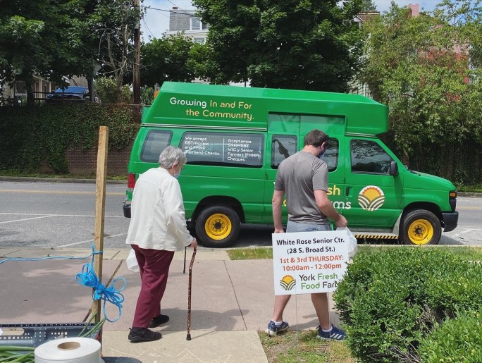 Mobile Produce Market volunteer helping elderly customer, July 2020