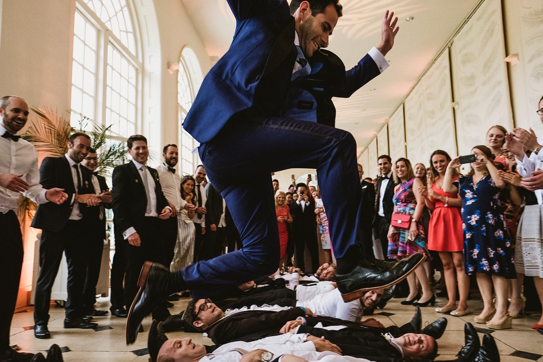 Kew Gardens Wedding Photography London. Groom jumping over the groomsmen, Jewish dancing.