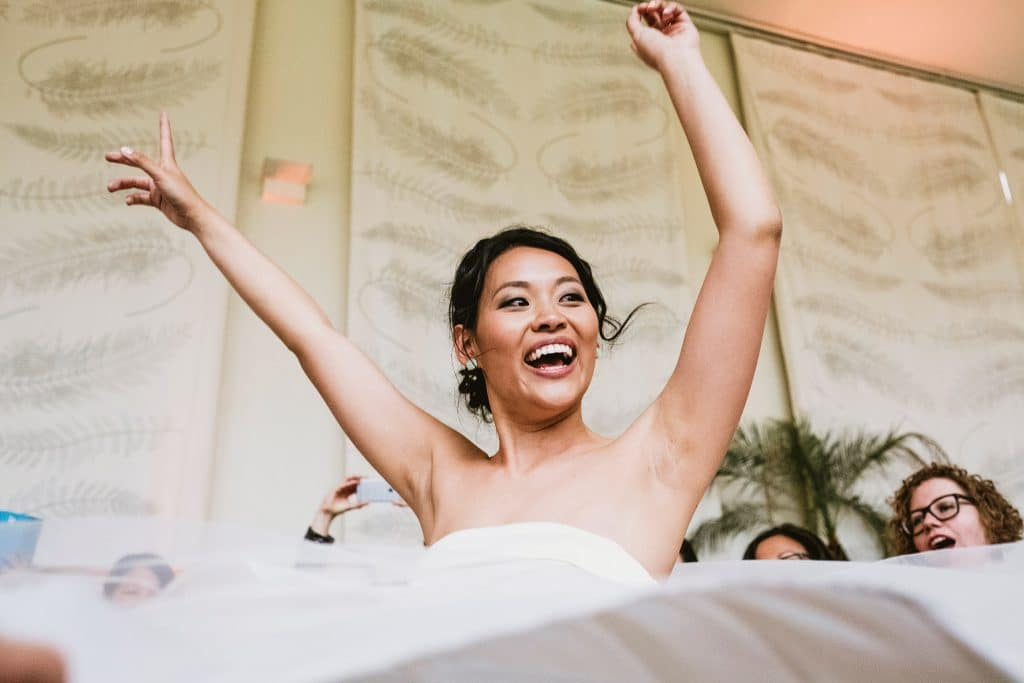 Bride dances with her arms raised in the air surrounded by female guests during a Jewish wedding in the Orangery at Kew Gardens
