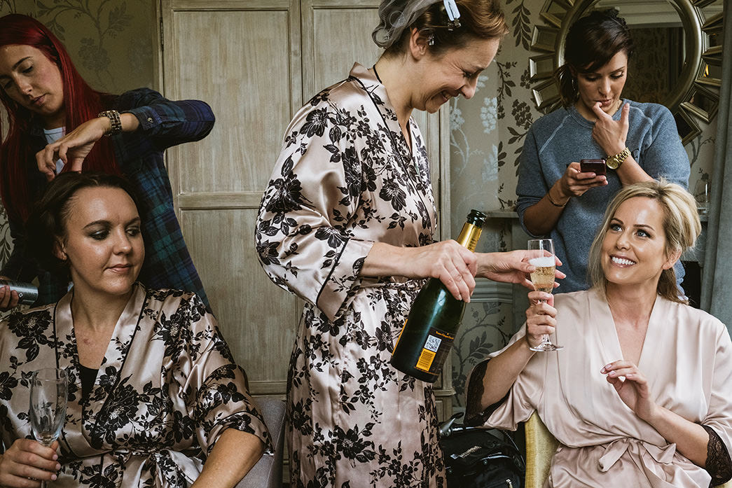 Morden Hall bridal preparations. Bride being passed champagne.