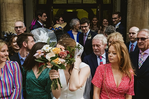 The Old Finsbury Town Hall Photography guests outside bride hiding behind bouquet