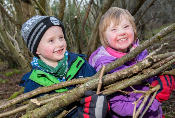 Two children holding branches and smiling
