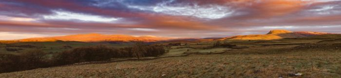 Panoramic shot oof the sun coming up over the Three Peaks