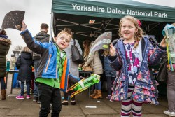 Children holding up their dark skies arts and crafts that they made outside next to the Yorkshire Dales marquee
