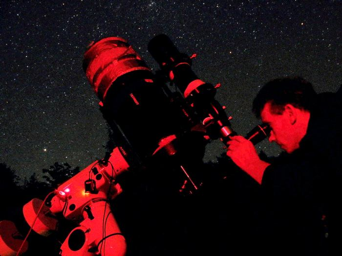 Astronomer Richard Darn looking through a telescope at the starry night above