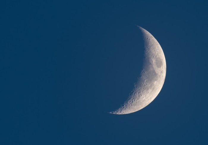 Close up shot of the crescent moon in a deep blue sky