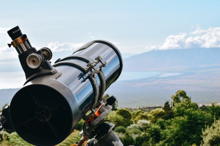 Close up of a large telescope over looking some hills in the day time