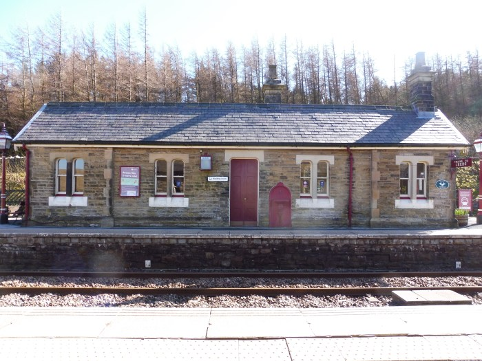 Photo shows the exterior of a waiting shelter at Garsdale. The door and drains are painted maroon whole the window surrounds are cream. The building is long and low with a slate roof
