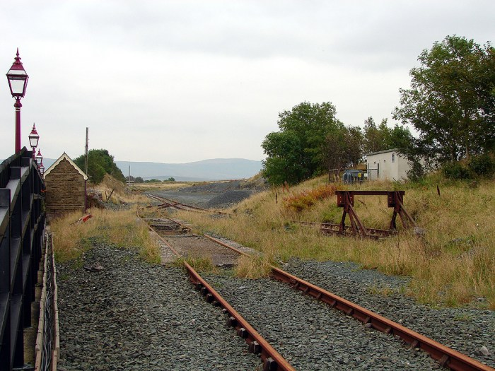 Photo shows a view of the sidings. There is some vegetation scattered around and part of a building is also visible.