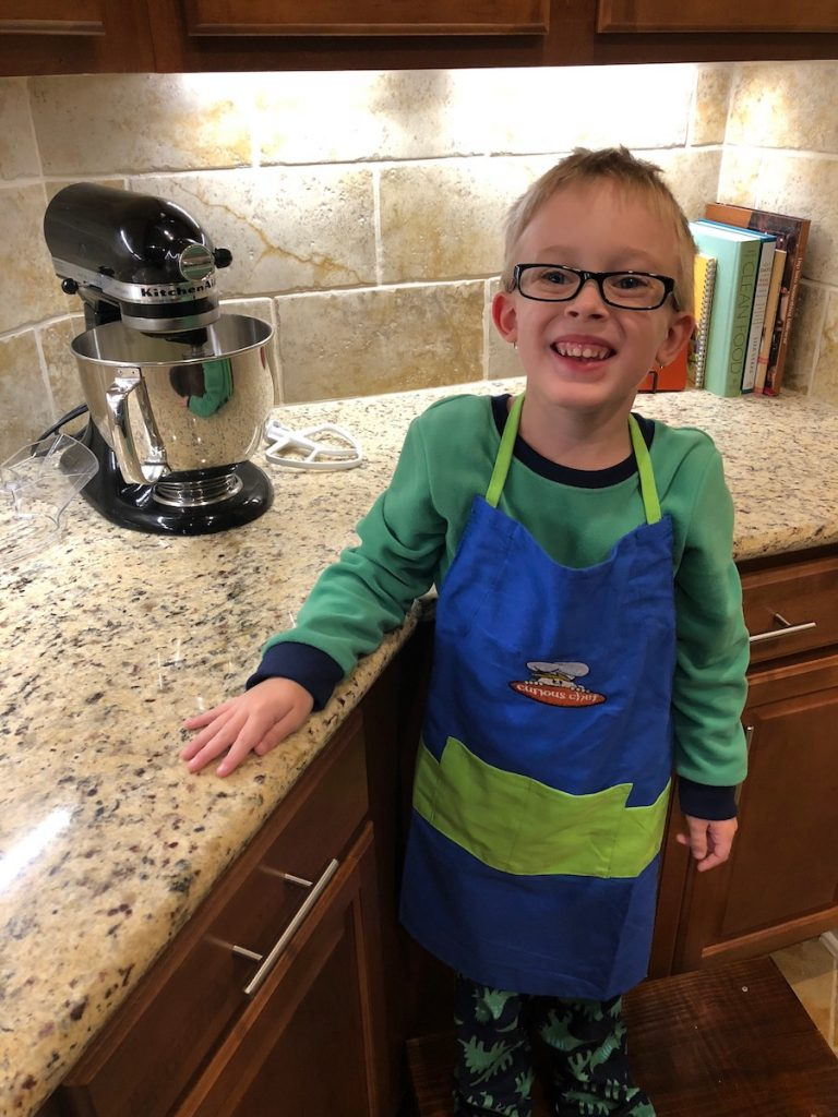 Young boy in a cooking apron next to a stand mixer on the counter
