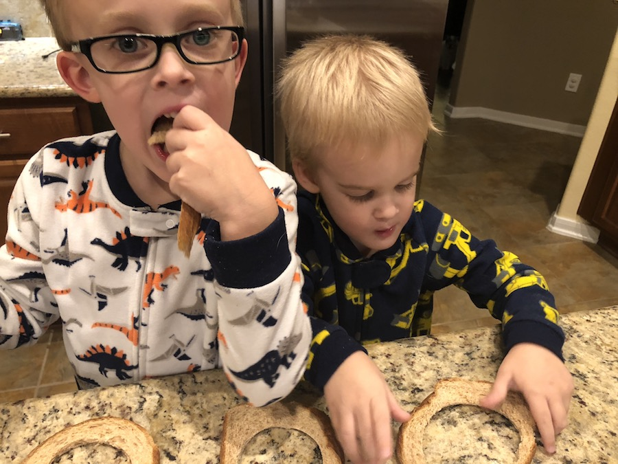 Two young boys in pajamas eating the scraps of bread