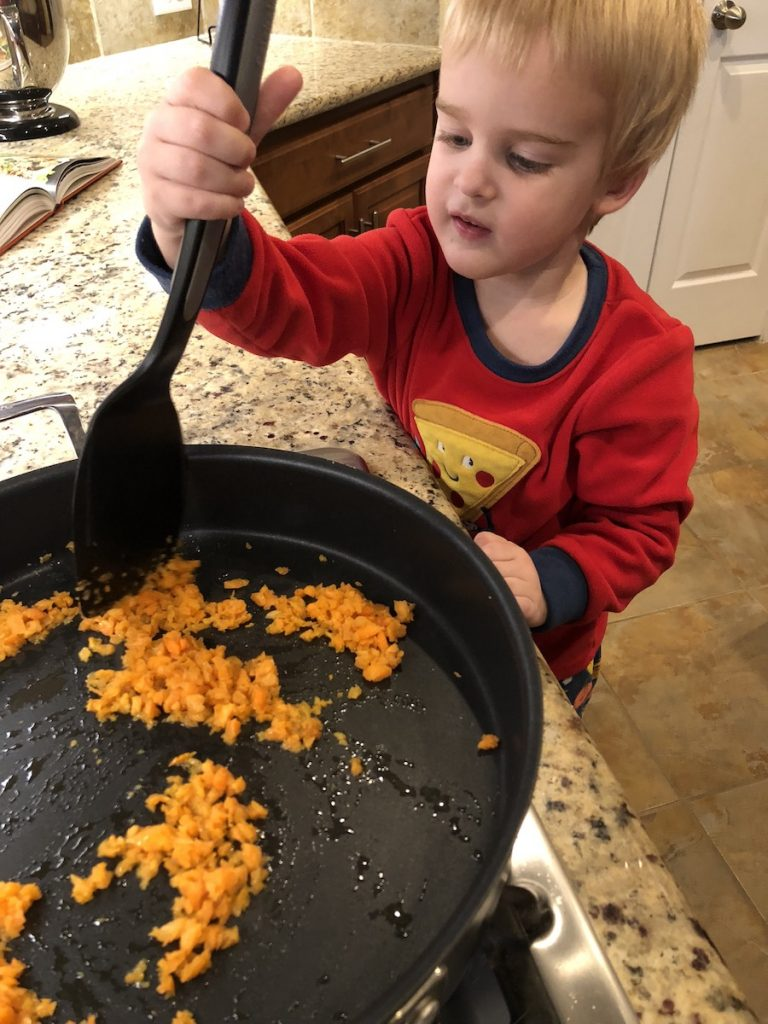 Young boy using a flat spatula to stir chopped carrots in a large skillet over a gas stovetop