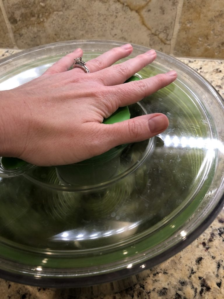 Woman's hand pressing the plunger of a salad spinner