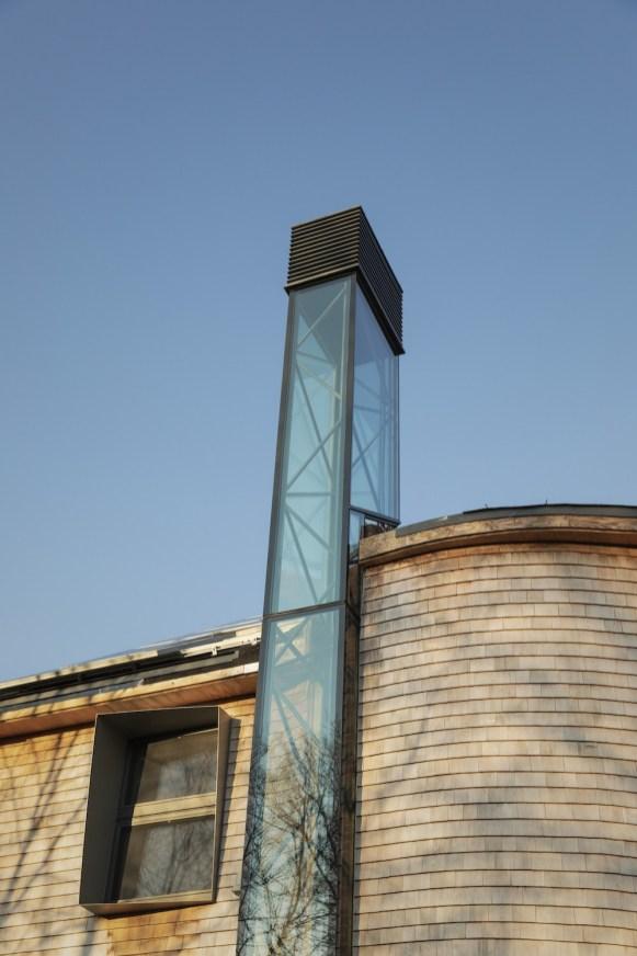 Un camino solare permette la ventilazione naturale. L'involucro vetrato è orientato verso il sole e carica un elemento termico di mattoni riciclati per favorire la ventilazione nello spazio per eventi nel seminterrato. Le sezioni vetrate del camino solare consentono alla luce naturale di entrare nella tromba delle scale