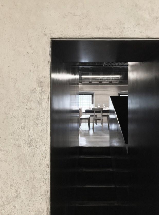 Il passaggio tra la sala all'interno dell'ex chiesa e la sala dell'ex carcere caratterizzata dall'uso di ferro nero