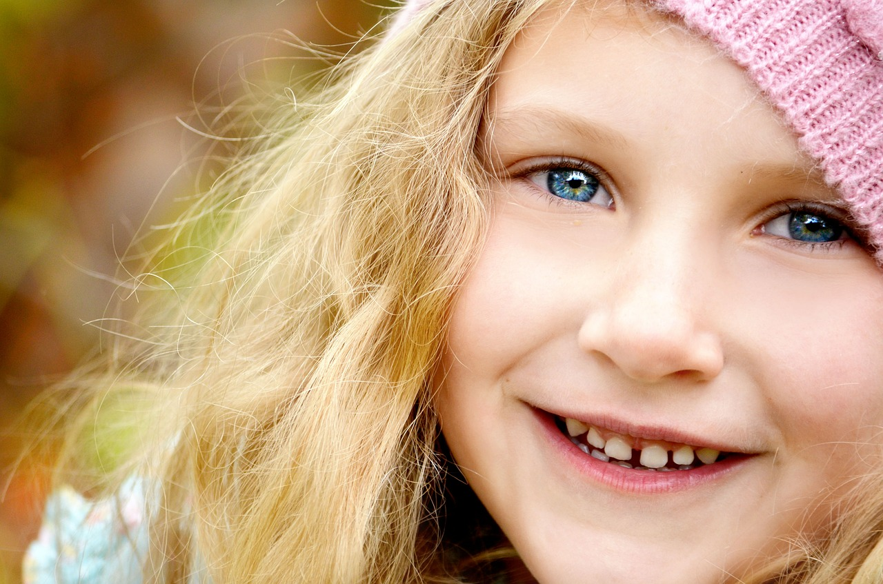 Blond girl with blue eyes smiling with a pink hat Younfolded blog