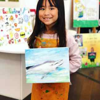 student showing art dolphin