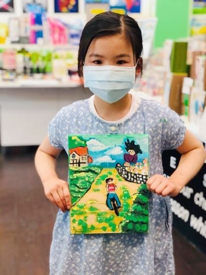 student holding a canvas painting