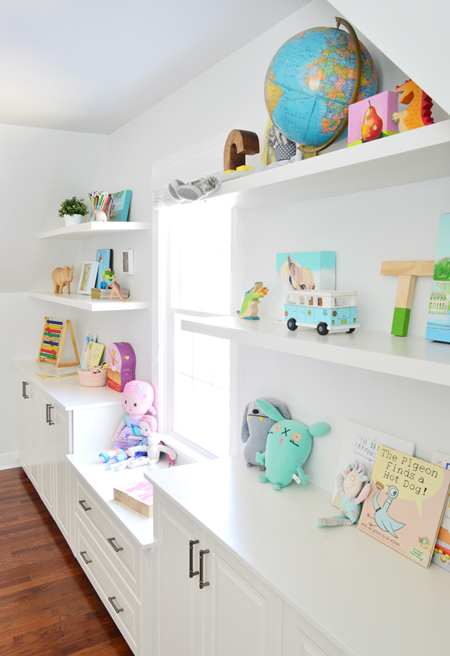 White floating shelves under sloped ceiling filled with toys books and kids objects in a playroom