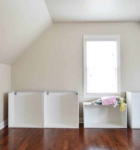 Room with sloped ceiling and Ikea cabinet boxes being built, with a girl's doll using one as a window seat