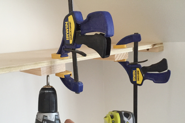 Screwing on a top plywood piece for thin floating shelves using Irwin Quick Grip clamps to hold the in place