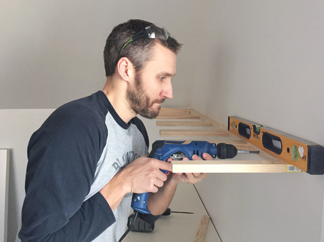 attaching brace piece for white floating shelves using a power drill driver and level